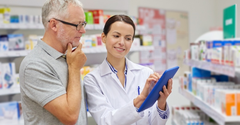 A man discusses his pharmacy savings card with a pharmacist to see what medications are covered