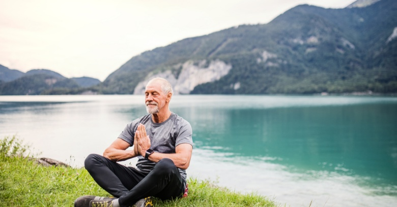 A man takes time to care for his health by meditating near a lake