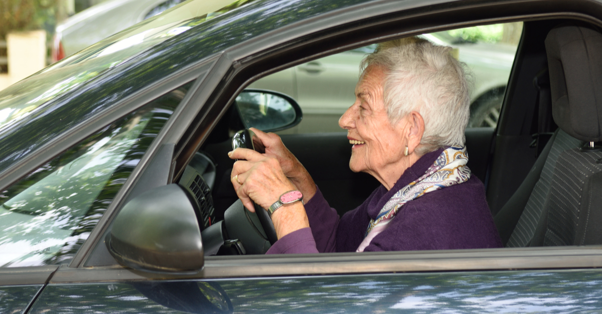 An older woman behind the wheel of a car.