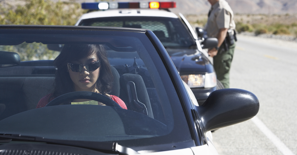 A woman gets pulled over by a police officer.