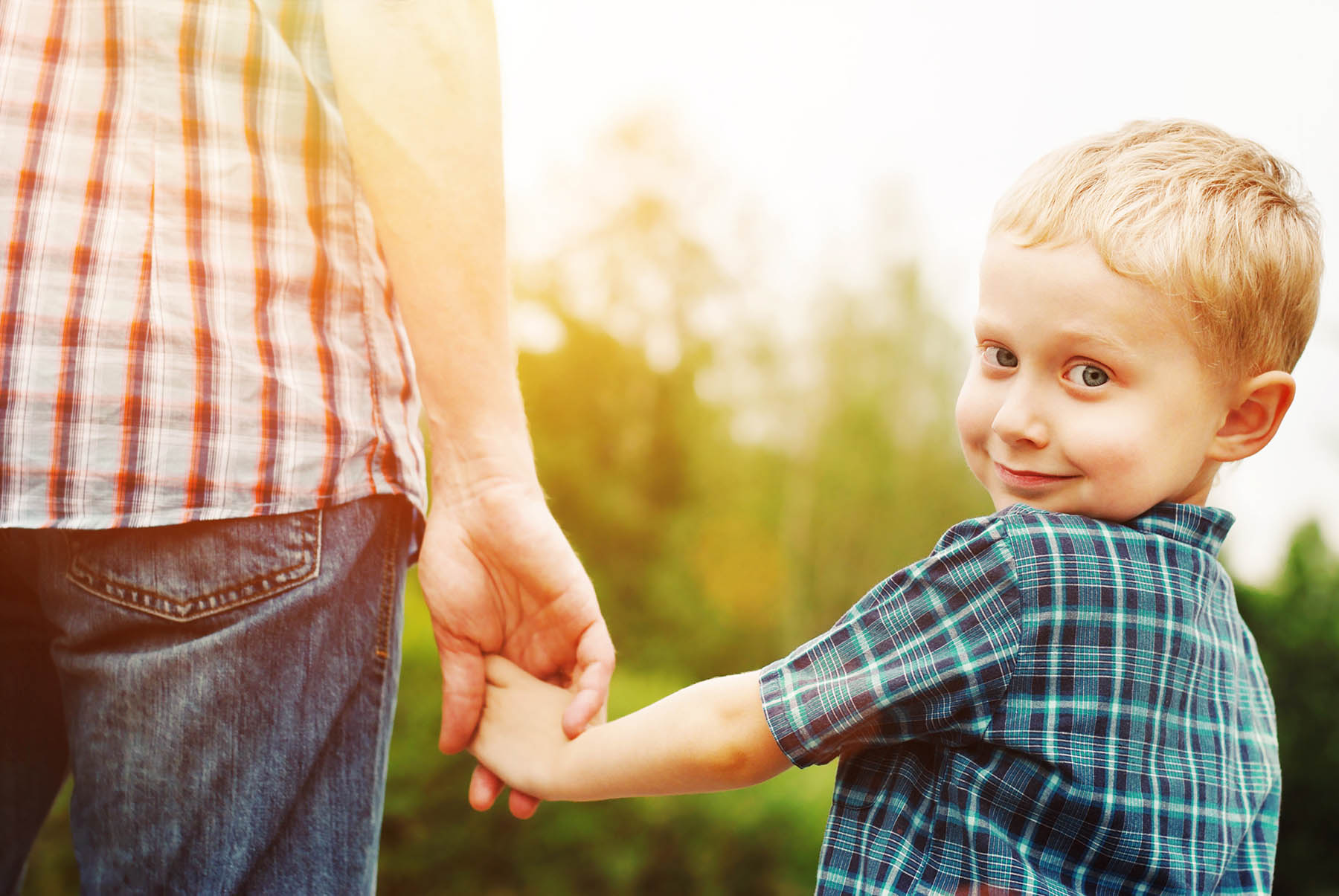 Boy smiling holding dad's hand