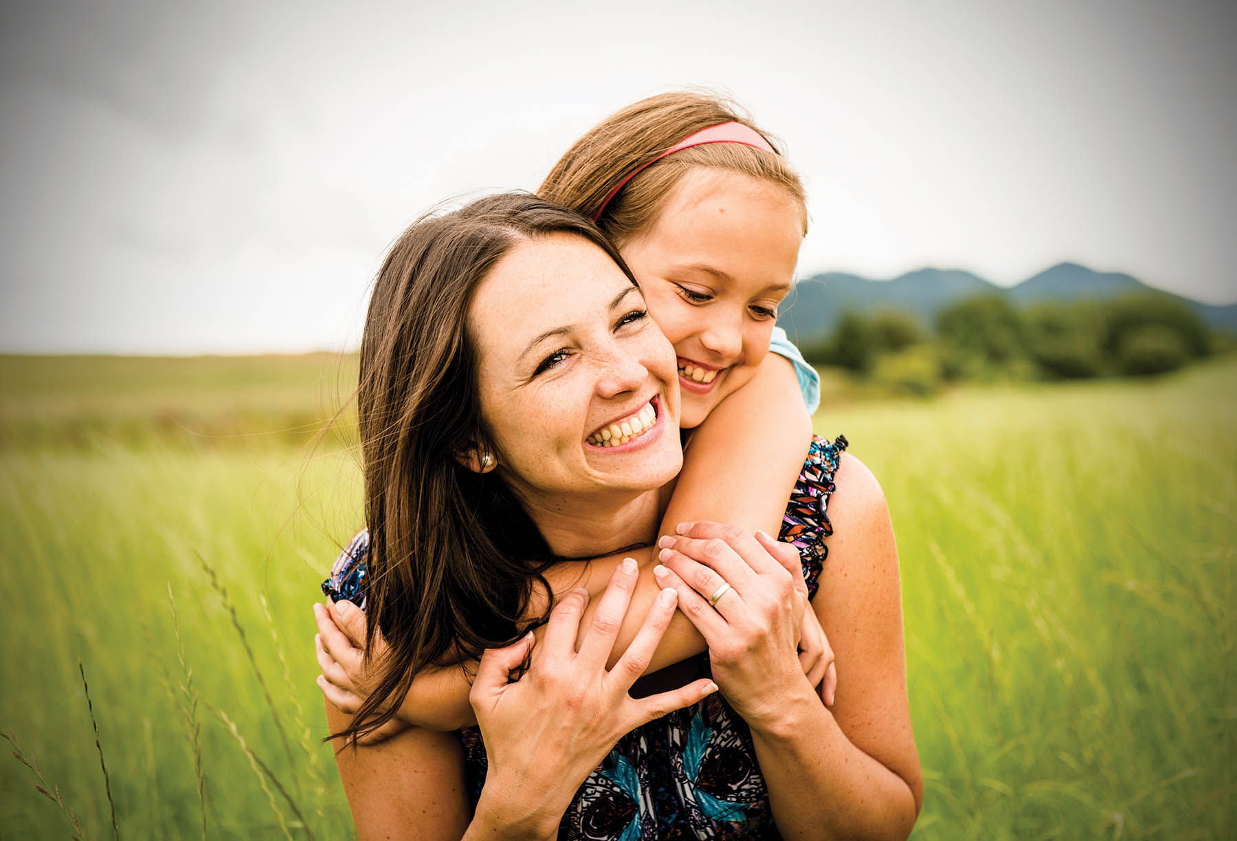 Mom and daughter in a grassy field