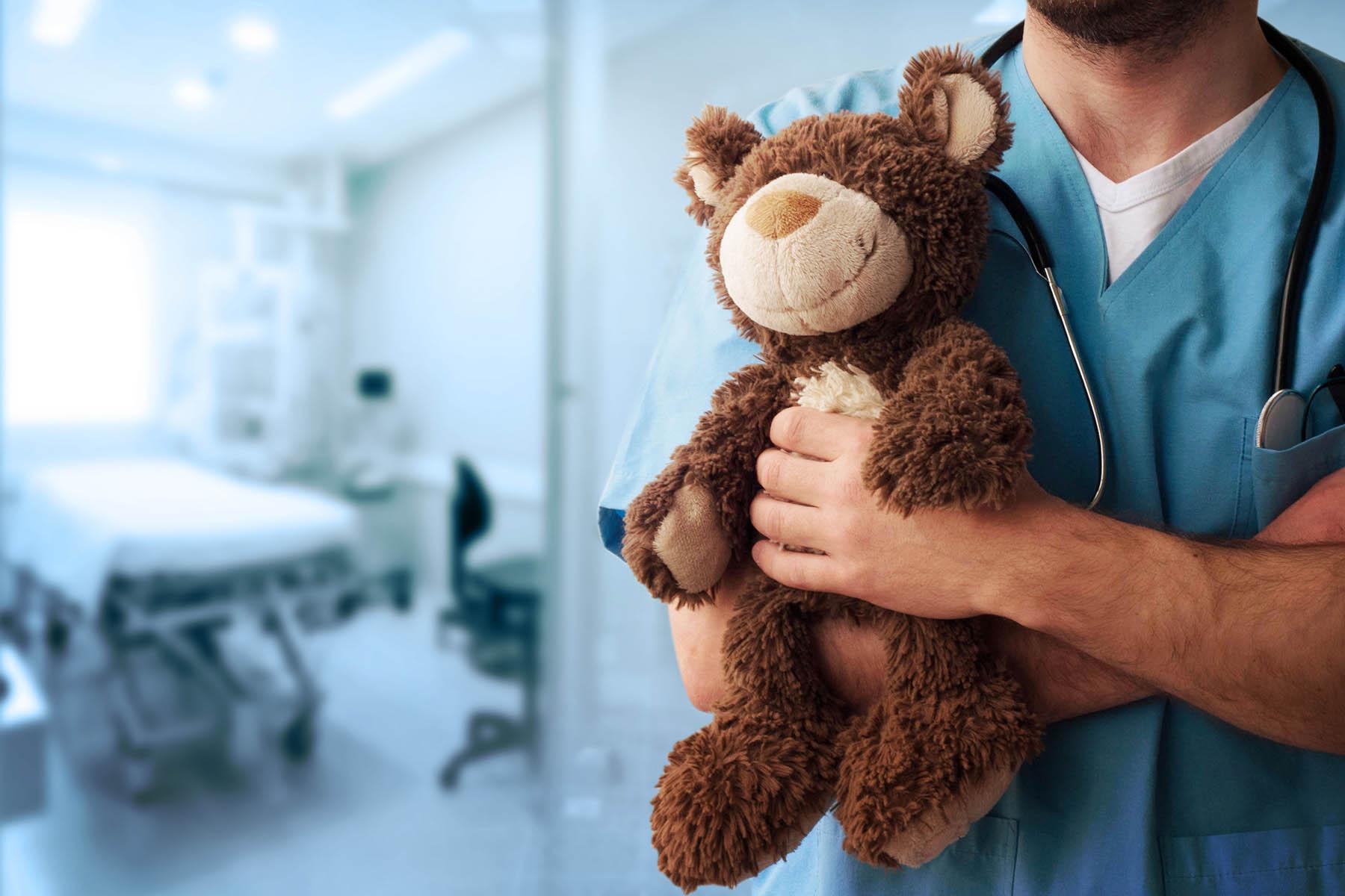 Doctor in hospital room holding teddy bear