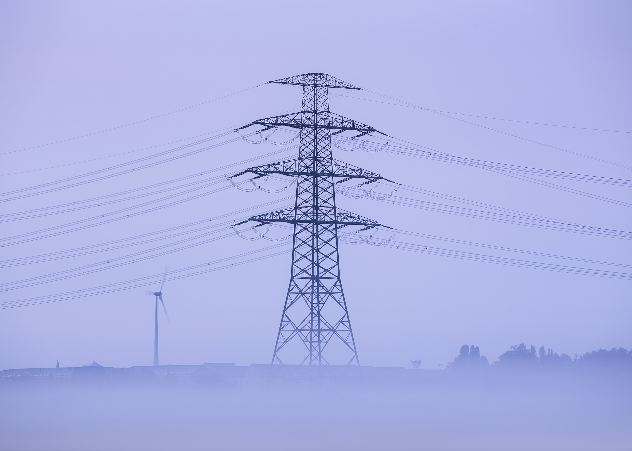 Power transmission tower in morning fog