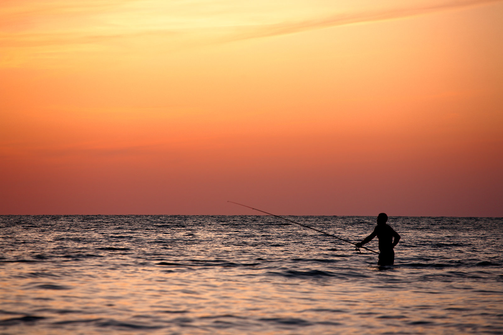 Fisherman in the sea at sunset