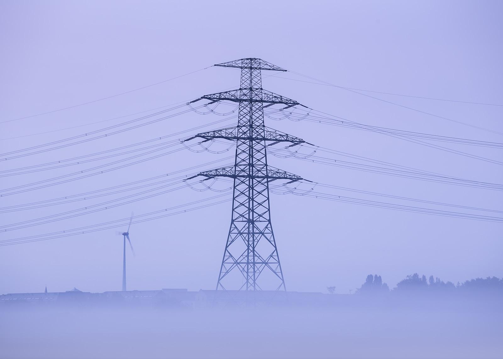 Power transmission tower in morning fog