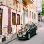 Black Glinting 2016 Volkswagen Jetta Along The Pavement Of Street With Old Buildings In Summer Day