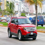 2017 Red Ford Explorer driving down street