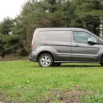 Ford Transit Connect on grass next to trees