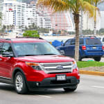 Red Ford Explorer driving down road with palm trees