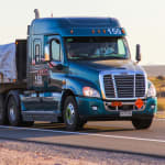 DTNA Freightliner Cascadia driving down a highway