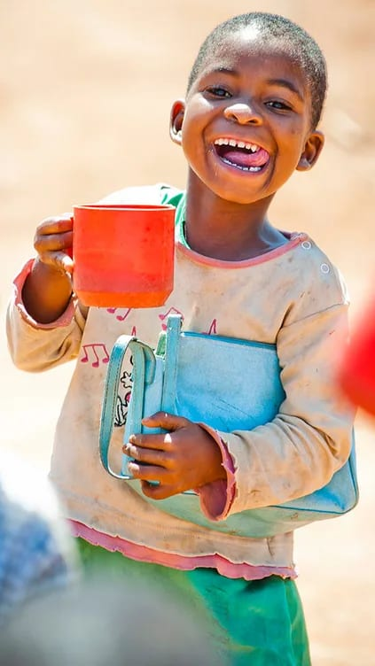 Young African girl smiling with a mug in her hand and a handbag under her arm