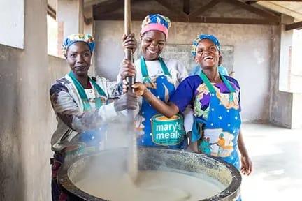3 Malawian volunteers cooking porridge