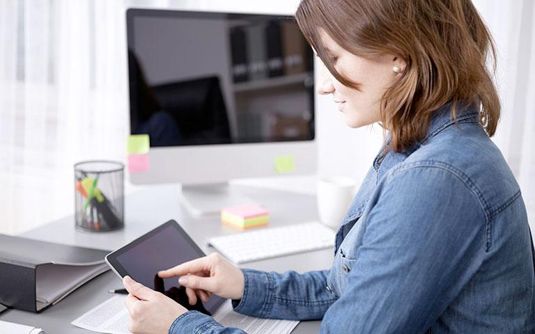 Photo of person working on a tablet device