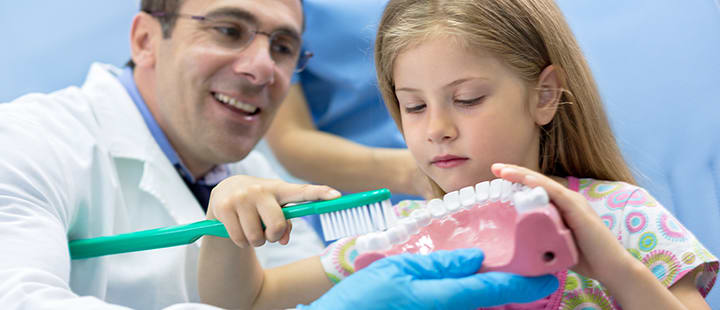 Dentist showing patient the hygiene appointment is more than just a cleaning