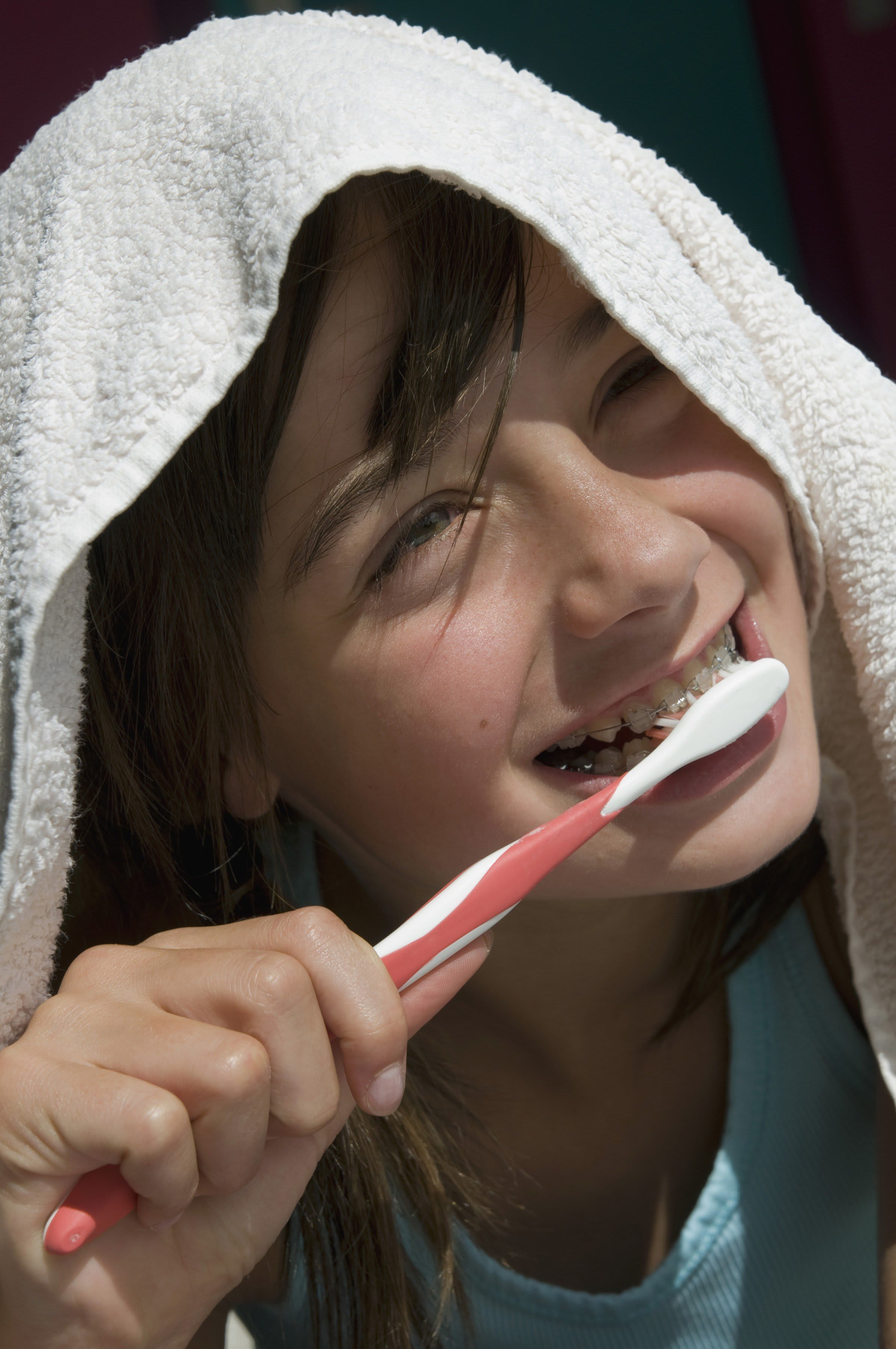 Smiley girl brushing her teeth with a manual toothbrush