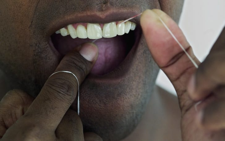 Close up photo of man flossing his teeth