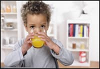 Photo of young child sipping acidic orange juice without a straw.