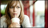 Photo of young lady sipping beverage through a straw.