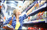 Photo of woman consumer reaching for products on store shelves.