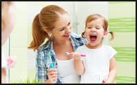 Photo of mother and young daughter practicing good oral hygiene.