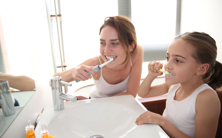 Two children looking in a mirror brushing their teeth