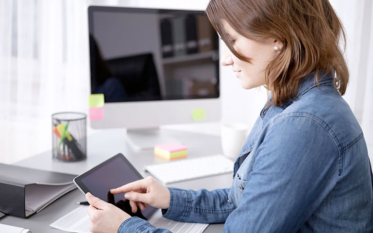 Photo of woman sat at office desk holding a tablet device