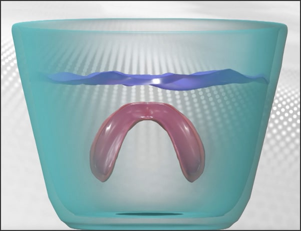 Image showing denture submersed in cool water to hydrate adhesive