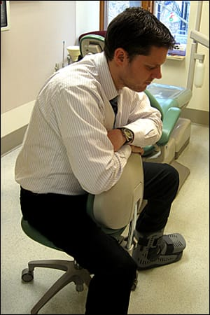 Image: Figure 5 depicts a patient sitting upright in a comfortable position with the arms crossed forward over a chair back.