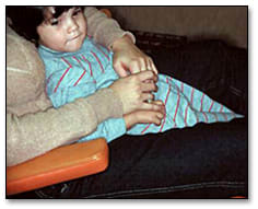 Image: Child in the parent's lap in examination chair.