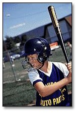 Image: Youth baseball player wearing proper batting helmet with protective face cage.