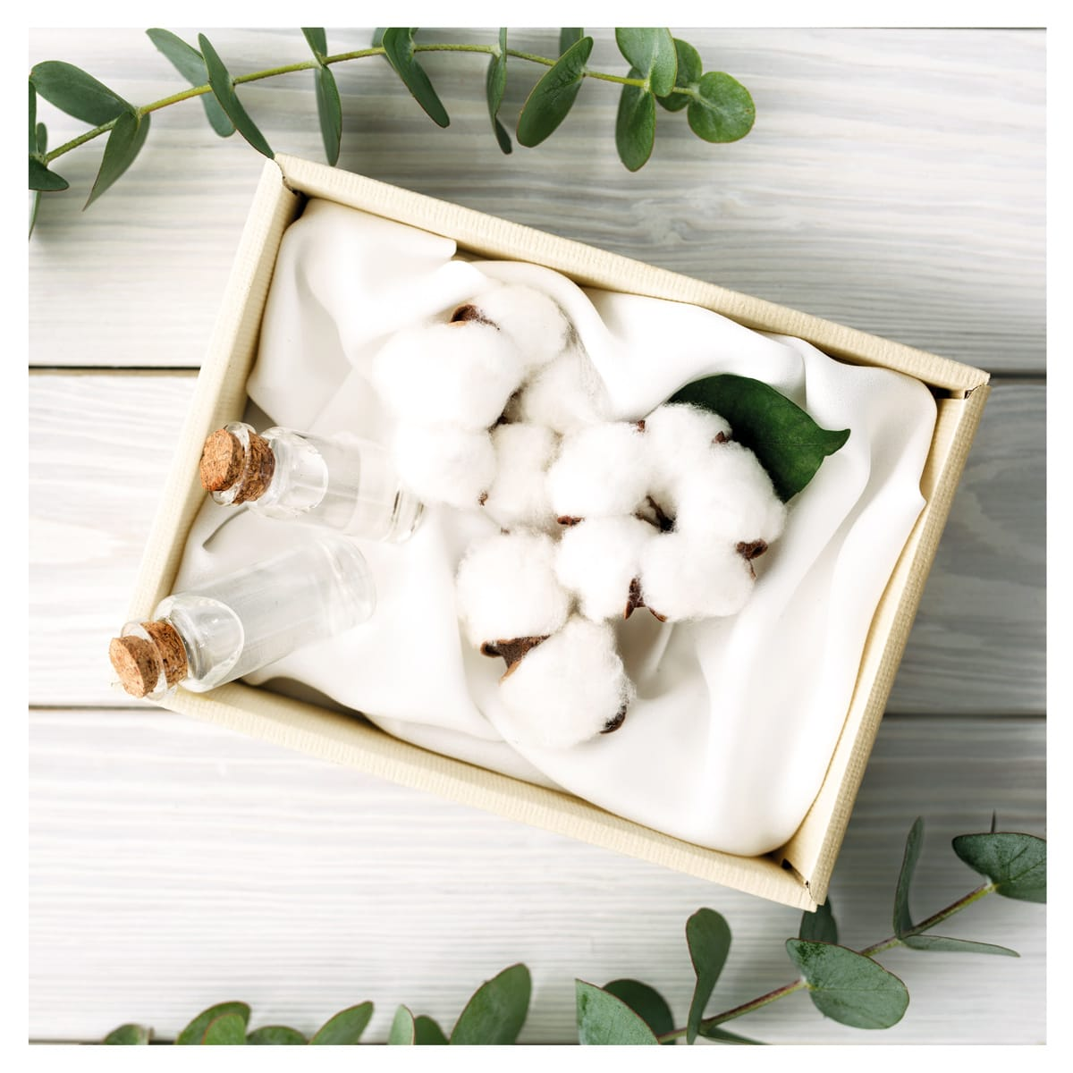Box of pads and cotton flower on a wooden background