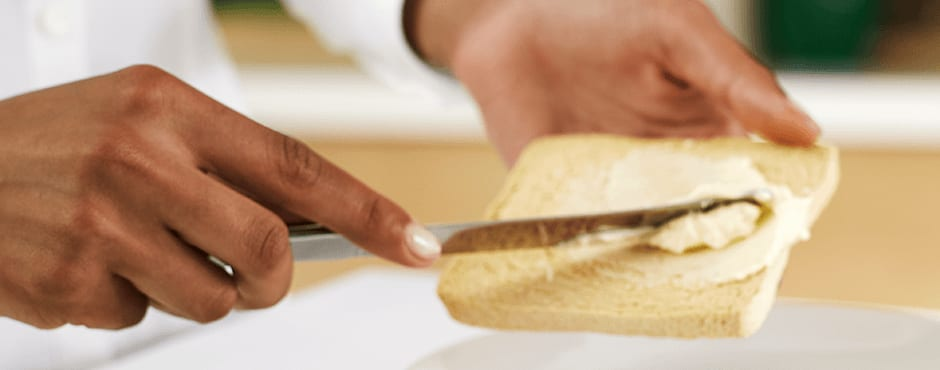 Hands buttering a bread with a knife