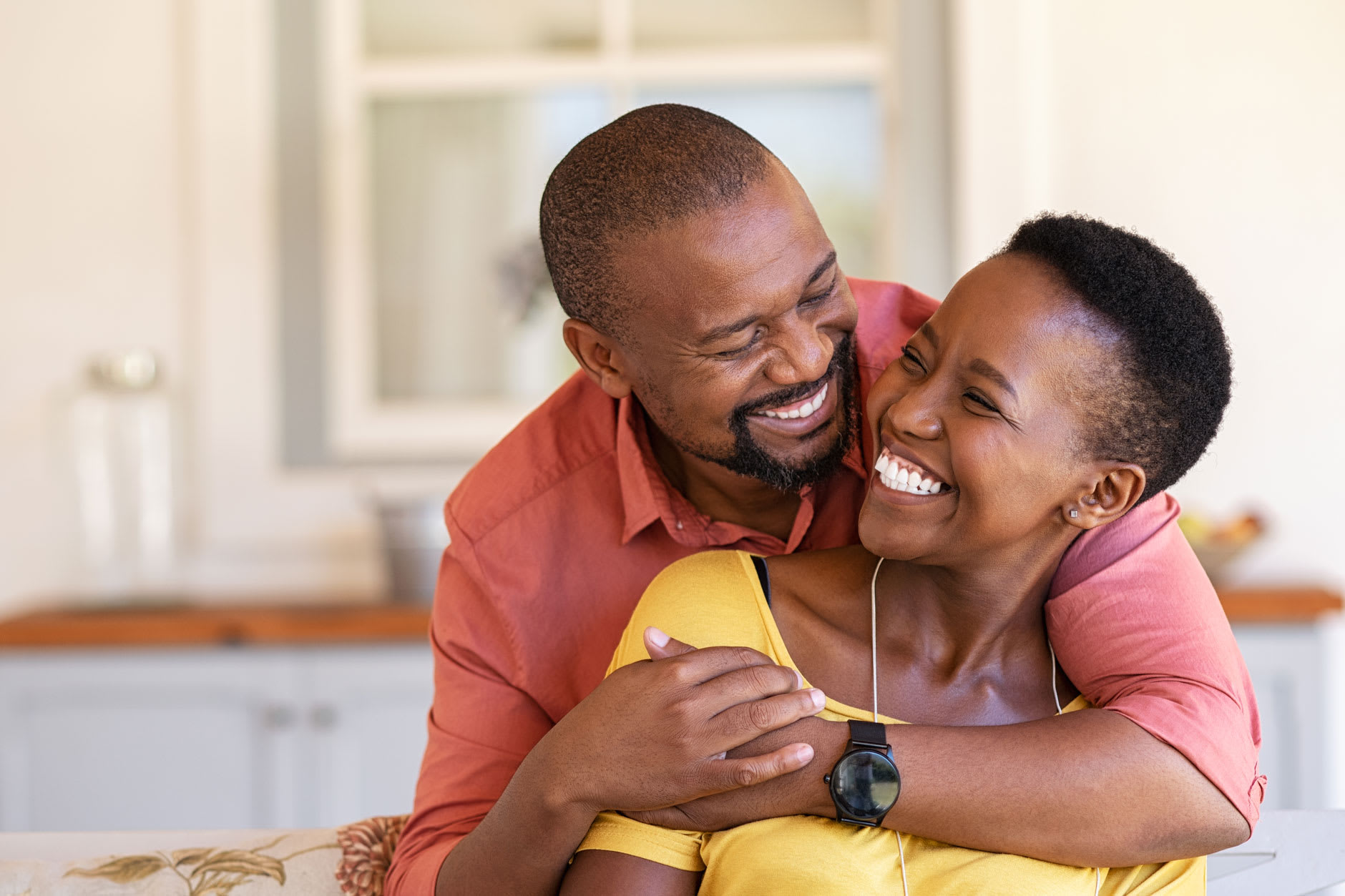 A couple in their 40s are hugging and smiling, the woman is wearing dentures, but is happy and confident because thanks to Fixodent, she knows how denture adhesive works.