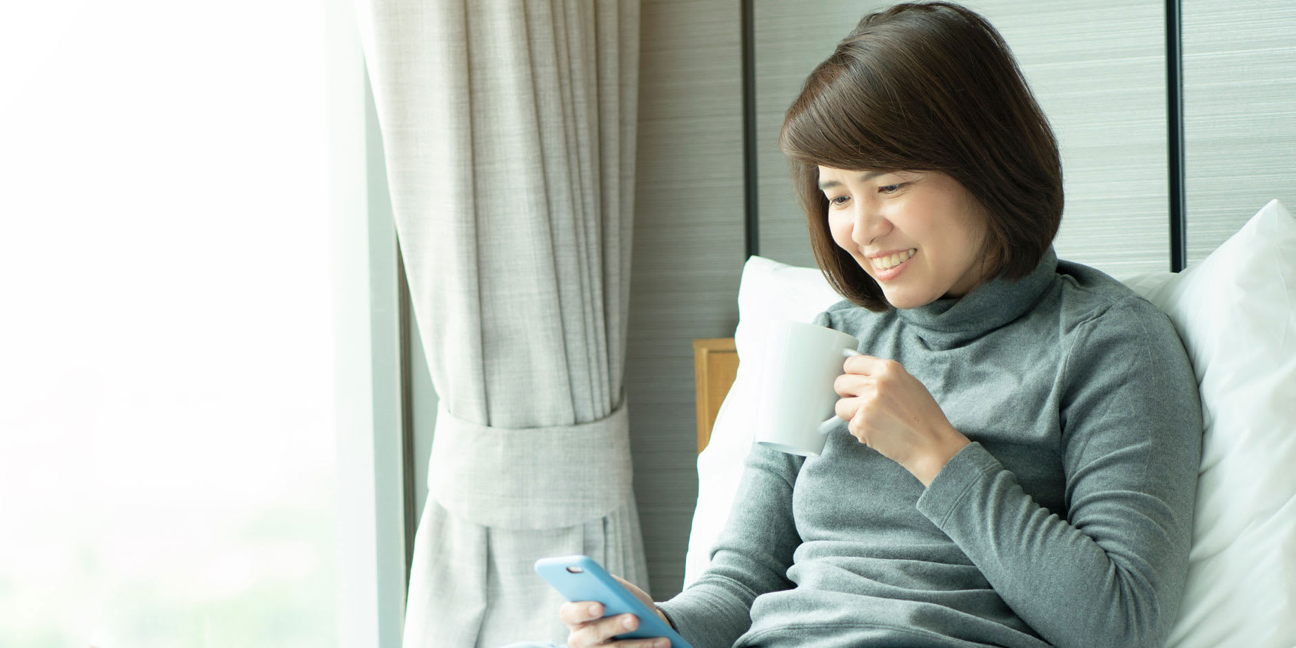 A woman in her 40s is browsing her smartphone for the costs of repairing and relining dentures.