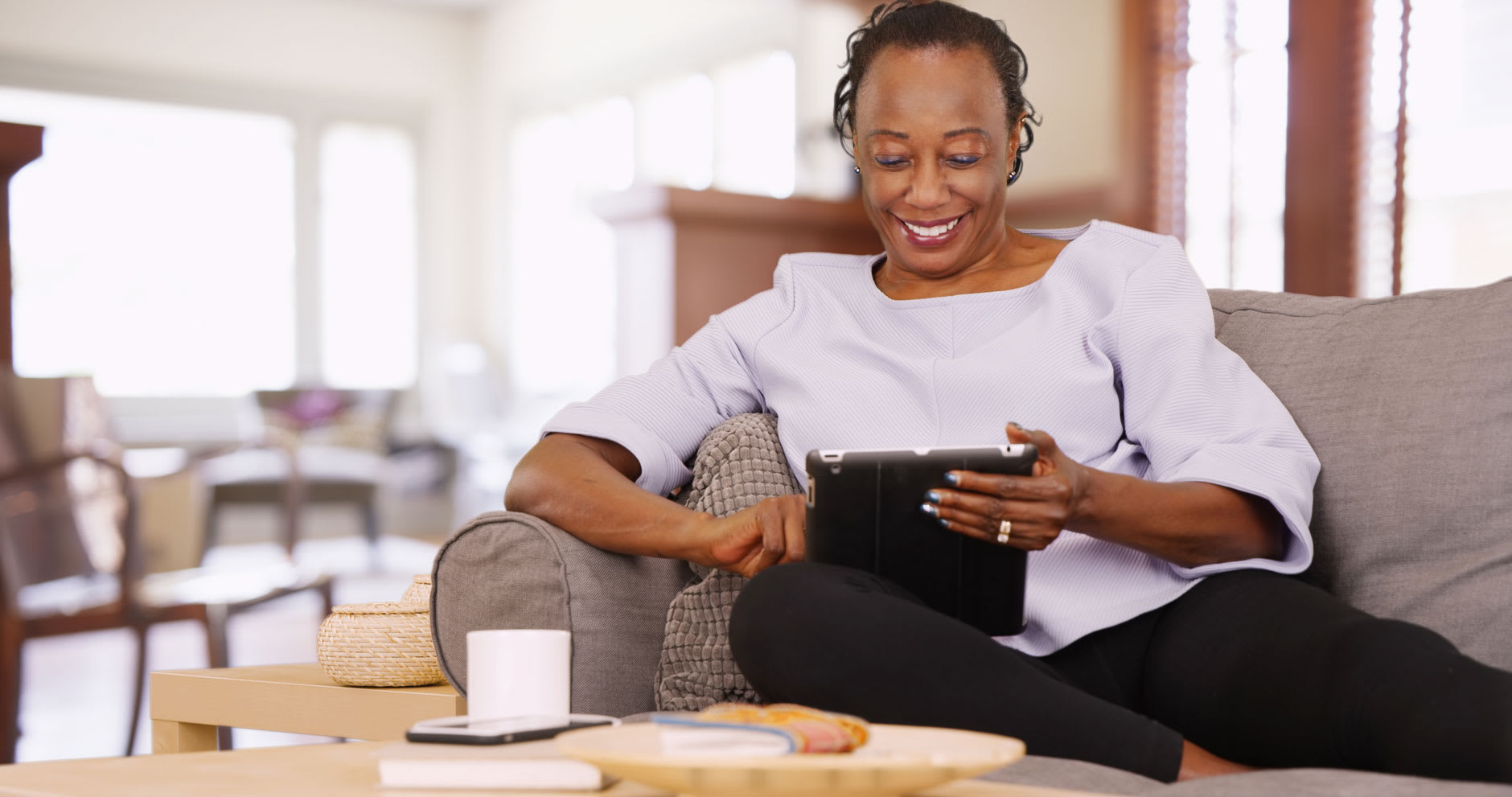 A woman is sitting on a grey sofa looking at an iPad and smiling confidently.