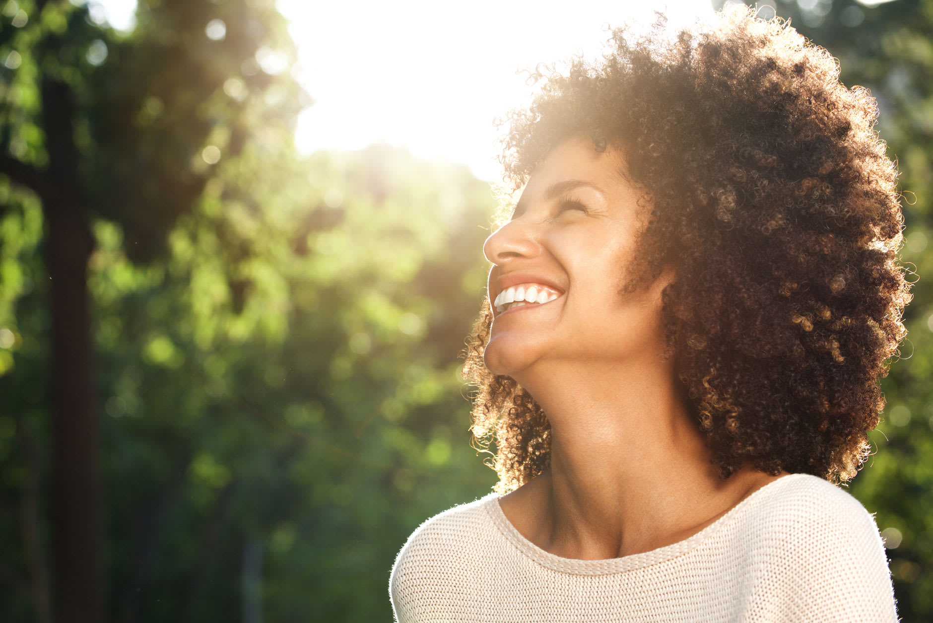 A woman in her 30s is smiling outdoors as she feels secure wearing dentures with Fixodent, which makes it easier for her to choose between dentures or implants.