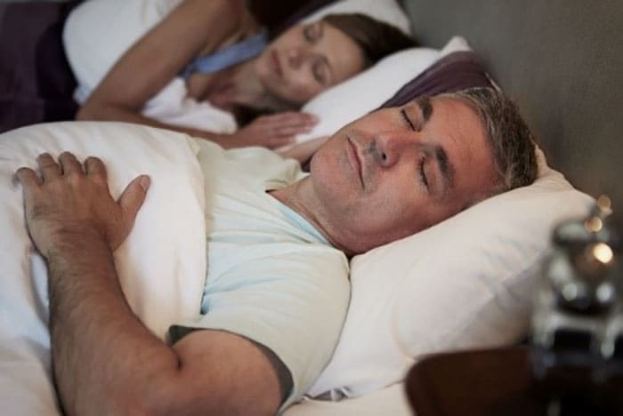 A couple in their 40s sleep soundly after taking their dentures out for the night as they know that the answer to can you sleep in your dentures is no.