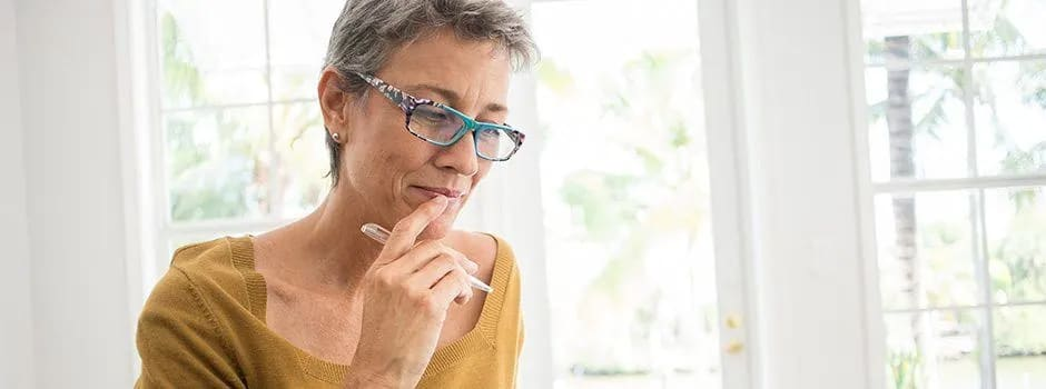 A woman in her fifties wearing glasses in a bright room holds a pen and her hand to her mouth, thinking deeply.