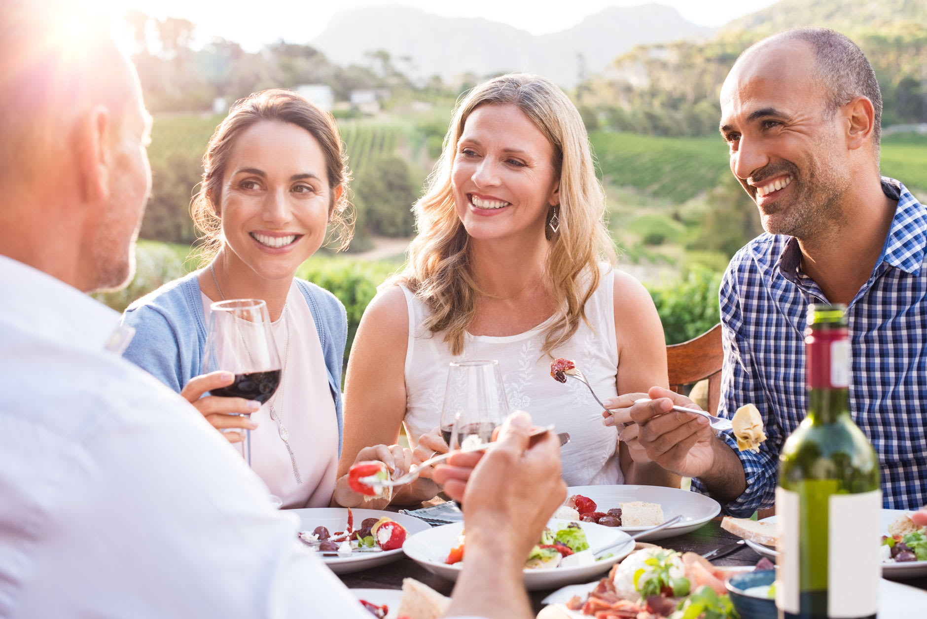 A group of friends are eating and drinking in a vineyard, they are smiling and one of them is wearing a partial denture. He is confident as he knows about the different types of partial dentures and uses Fixodent.