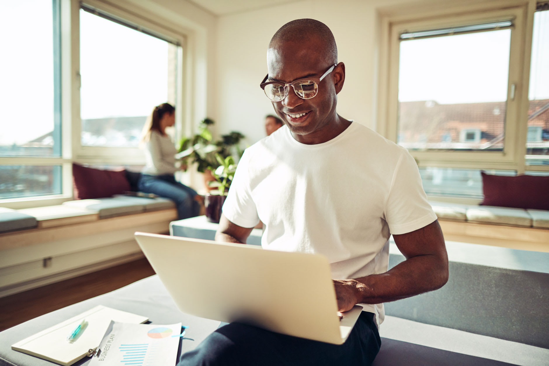 A man in glasses wearing a white shirt sits in an office reading a guide on how to clean and care for dentures on his laptop.