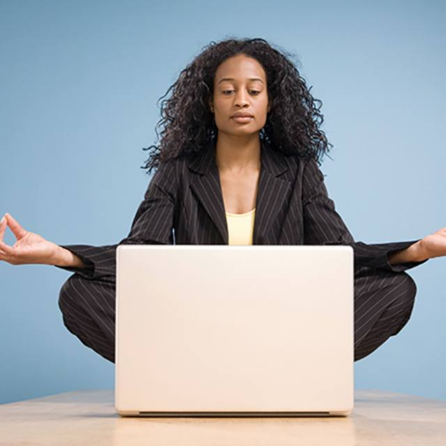 Young lady meditating in front of her laptop