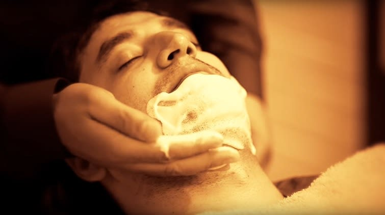 The barber applies a thick lather of shaving cream to the face, to lubricate the skin and raise the beard.