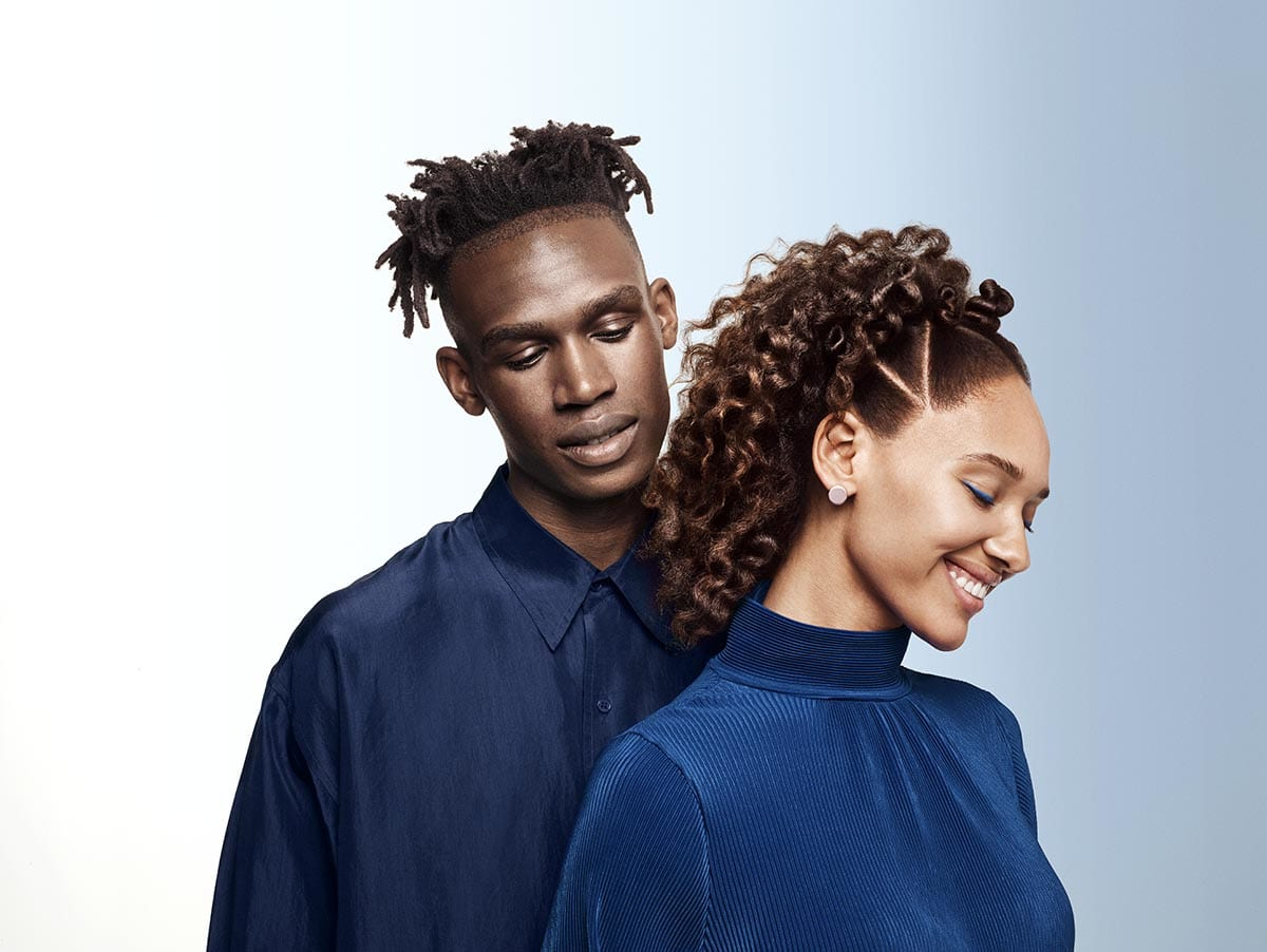 Woman and man with afro hair smiling