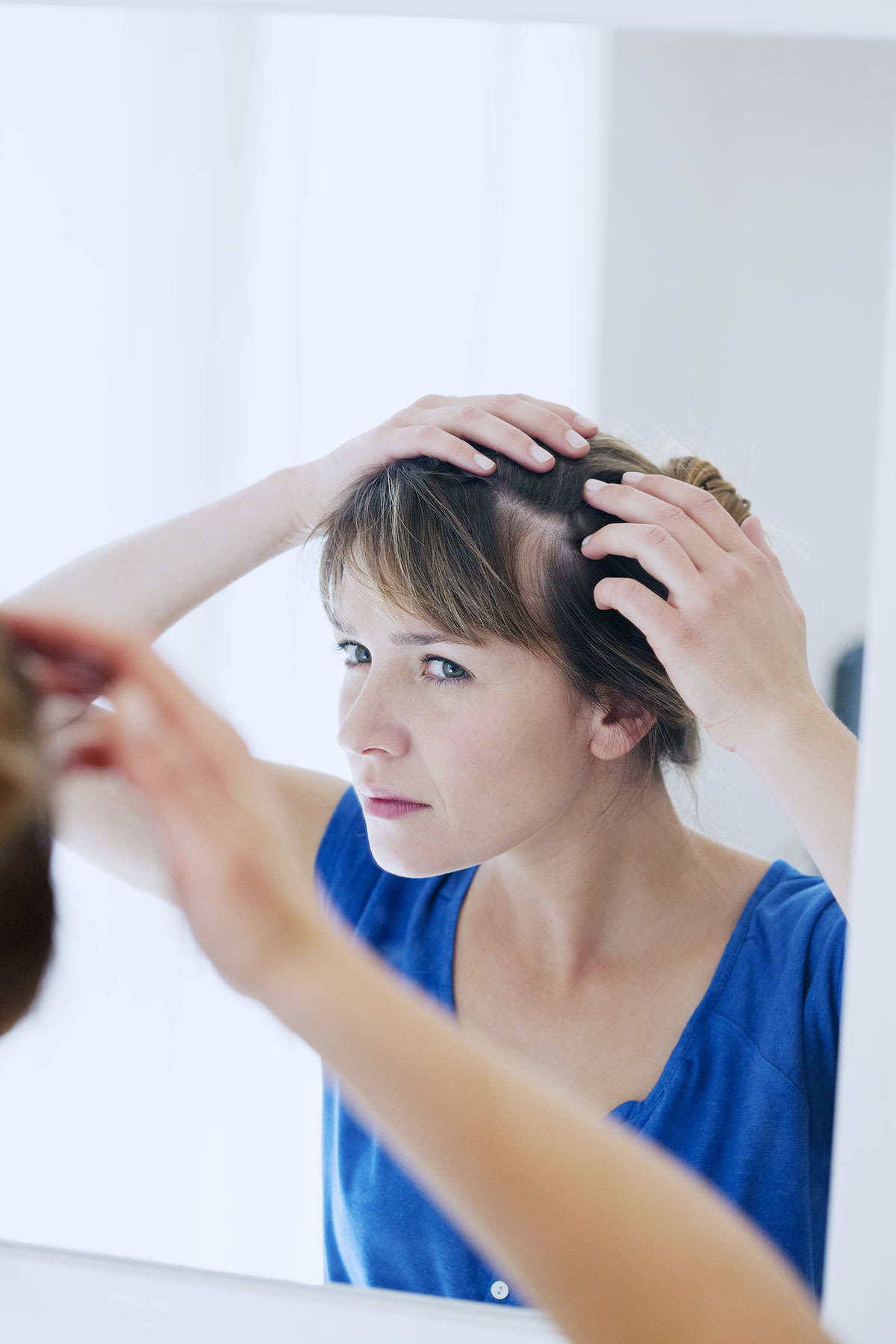 Woman looking at scalp in mirror