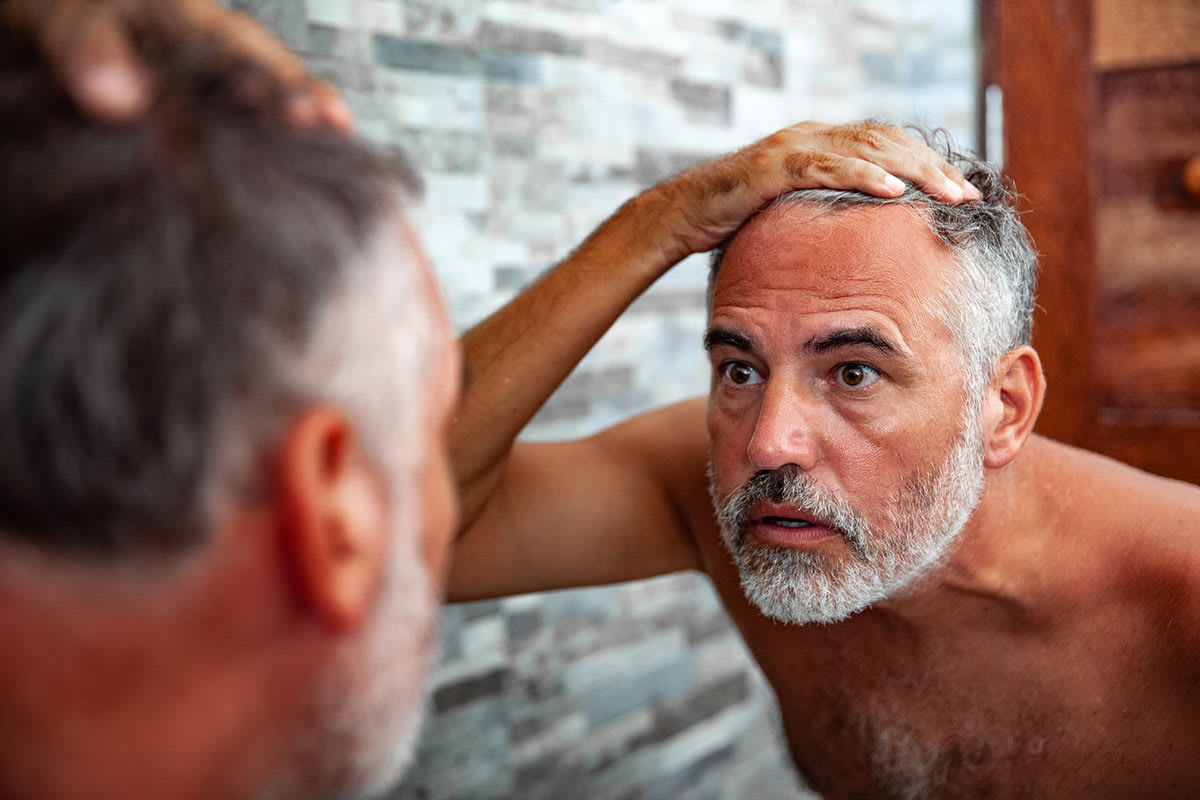 Man with beard looking at himself in mirror