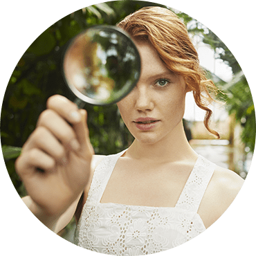 A woman holding and watching through a magnifier