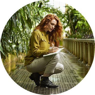 A woman with shiny hair takeing a note in a Royal Botanic Gardens, where Herbal Essences ingredients are certified