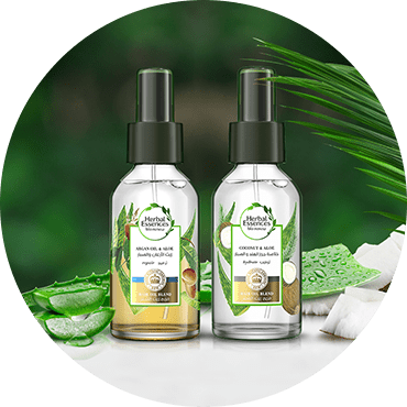 Two Herbal Essences Hair Oil Blend product bottles, with a natural blend of Argan and Coconut Oil, with Aloe vera and coconut ingredients in background