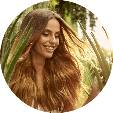 A smiling woman with strong and healthy hair in a field of Aloe vera (the key natural ingredient used in the Herbal Essences Potent Aloe Vera Collection)